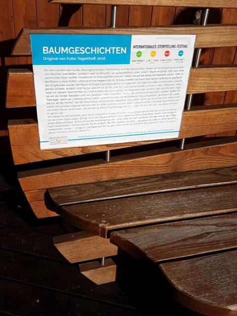 Farbphotographie, Sitzbank mit einer Tafel, Aufschrift Baumgeschichten von Folke Tegetthoff