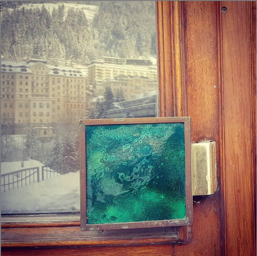 Tür mit Holzrahmen und grünem Griff, in deren Glasscheibe sich ein Hotel spiegelt