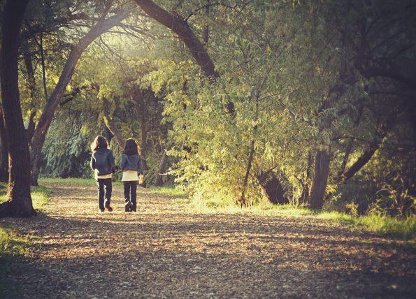 zwei Mädchen auf Weg neben Bäumen