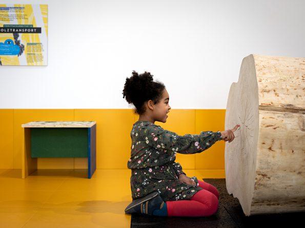 Mädchen in Museum zeigt auf großen liegenden Baumstamm - Ausstellung Alles Holz